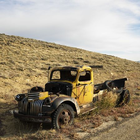 Old yellow dilapidated pickup truck sitting abandoned on hill.