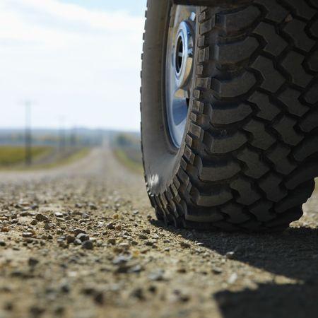south dakota: Basso angolo vista delle grandi camion pneumatico sulla strada sterrata nelle zone rurali del Sud Dakota.