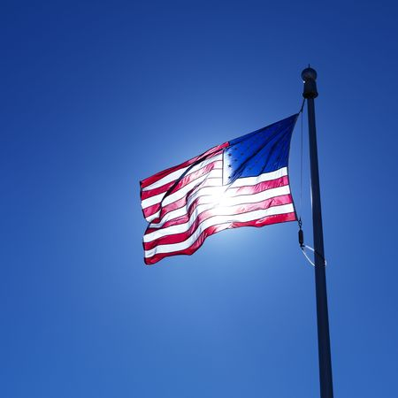 flagpole: American flag on flagpole waving against blue sky with sun shining through from behind.