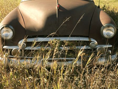 front end: Front end of old abandoned antique car in field.