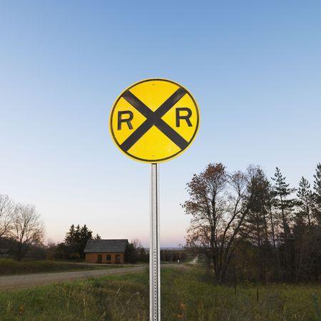 Circular yellow railroad grade crossing sign in rural setting. Stock Photo - 2235572
