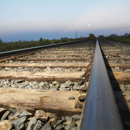 Low angle diminishing view of railroad tracks in rural setting at dusk. Stock Photo - 2235638