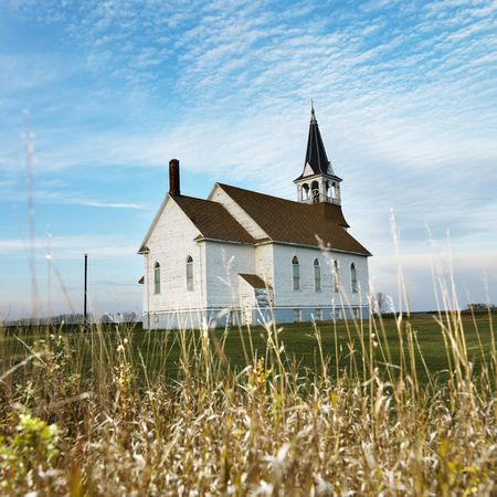 church bell: Small rural church in field with chipped wood siding. Stock Photo