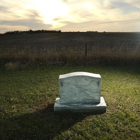 unmarked: Headstone marking grave in rural countryside at sunset.