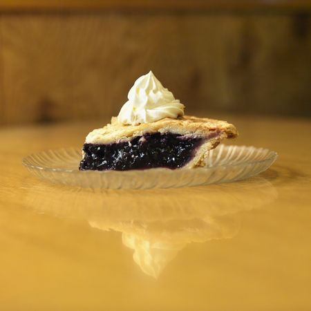 blueberry pie: Slice of blueberry pie on plate with whipped topping.