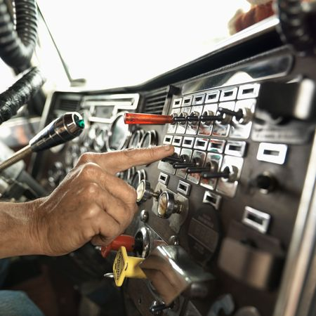 hand truck: Interior of mid-adult Caucasian male hand pressing switch on dashboard of a tractor trailer. Stock Photo