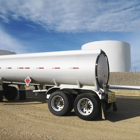 18 wheeler: Side view of fuel tanker truck with fuel tank farm in background.