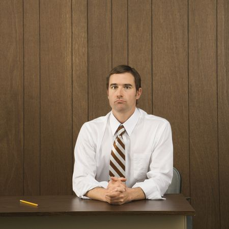 Mid-adult Caucasian male sitting at desk with pencil beside him. Stock Photo - 2448536
