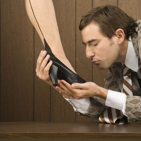 Mid-adult Caucasian male holding Caucasian female shoe and preparing to kiss it. Stock Photo
