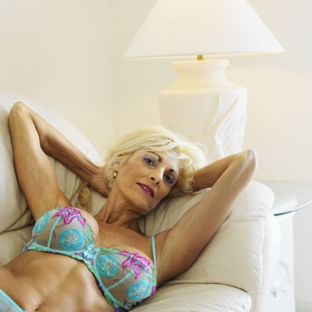 Tan Caucasion blonde middle-aged woman seductively lying in underwear on couch with arms raised smiling at viewer. Stock Photo - 2388792
