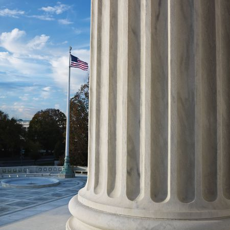 supreme court: Column of Supreme Court building with American flag in Washington DC, USA.