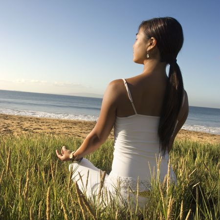 Young Asian female sitting on beach meditating and looking out to ocean.