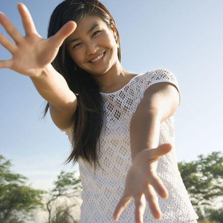 stretched out: Young adult Asian female with arms stretched out toward viewer.