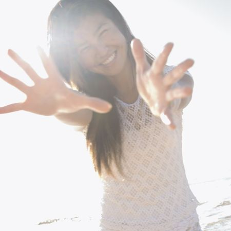 stretched out: Young adult Asian female with arms and hands stretched out toward viewer.