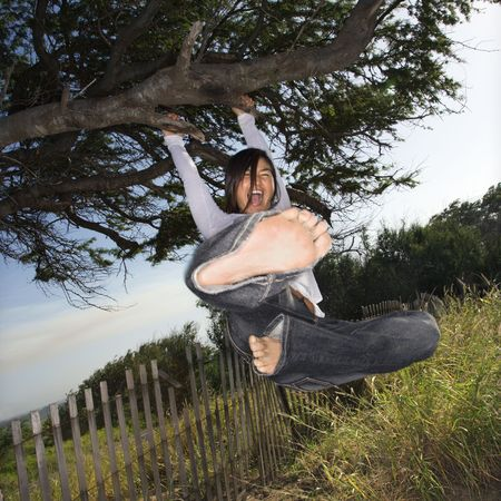 asian art: Young adult Asian female holding on to a tree and kicking towards viewer.