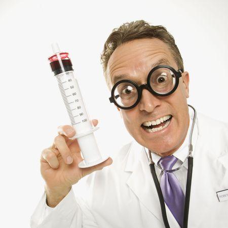 Mid-adult Caucasian male doctor wearing eyeglasses holding an oversized syringe. photo