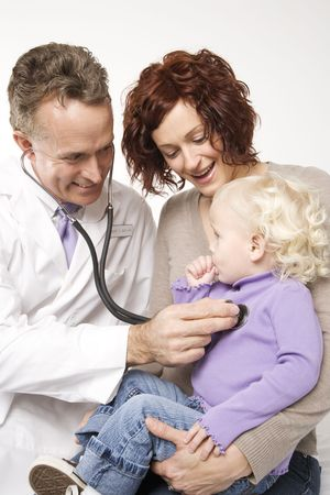 Middle-aged adult Caucasian male doctor holding stethoscope to female toddlers chest with mother watching. photo