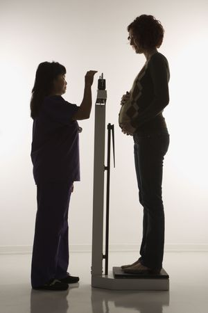 health facility: Pregnant Caucasian mid-adult woman being weighed by nurse.