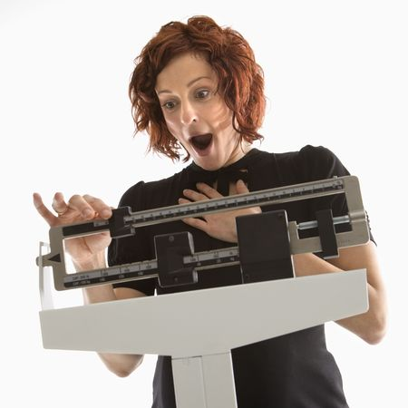 shown: Pregnant Caucasian mid-adult woman surprised by her weight shown on scale. Stock Photo