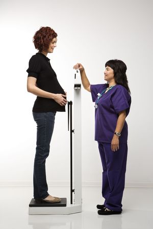 practioner: Pregnant Caucasian mid-adult woman being weighed by nurse.