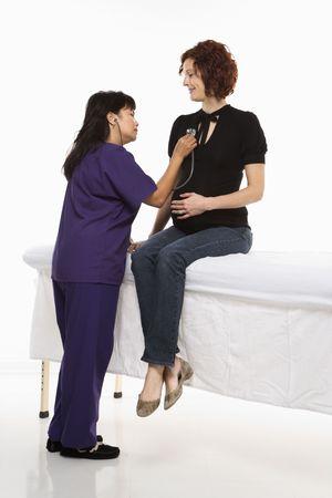 vital signs: Mujer cauc�sica embarazada del mediados de-adulto que hace que las muestras vitales sean comprobadas por la enfermera.