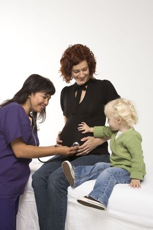 health facility: Nurse holding stethoscope on Caucasian pregnant womans belly as daughter holds hand on belly.