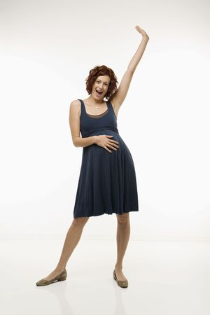 nurturing: Portrait of Caucasion mid-adult attractive pregnant woman standing with one hand on belly and other arm in air looking at viewer and smiling.