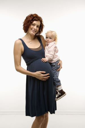 nurturing: Portrait of Caucasion mid-adult attractive pregnant woman standing, holding female toddler on hip and other hand on belly, looking at viewer and smiling.