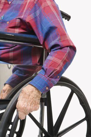 Caucasion male elderly hands gripping wheels of wheelchair. Stock Photo - 2245911