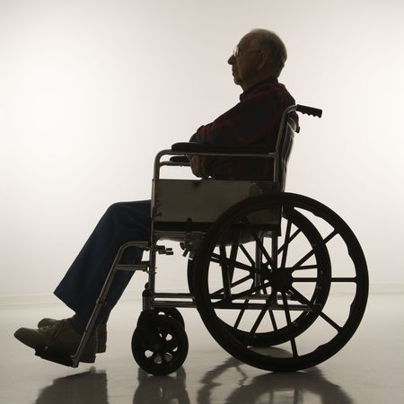 profile: Profile view of silhouetted Caucasion elderly man sitting in wheelchair.