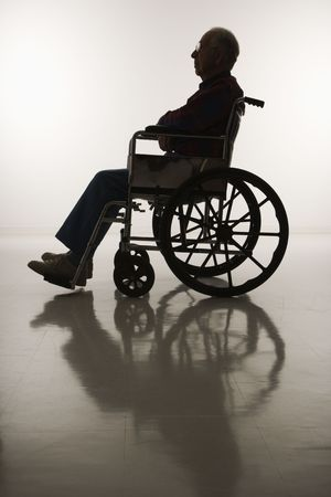 man profile: Profile view of silhouetted Caucasion elderly man sitting in wheelchair.