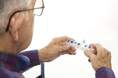 pill box: Profile view of Caucasion elderly man holding seven-day pill box with Thursday open. Stock Photo