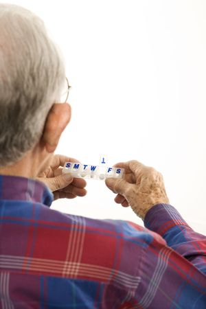 pill box: Back over the shoulder view of Caucasion elderly man holding seven-day pill box with Thursday open. Stock Photo