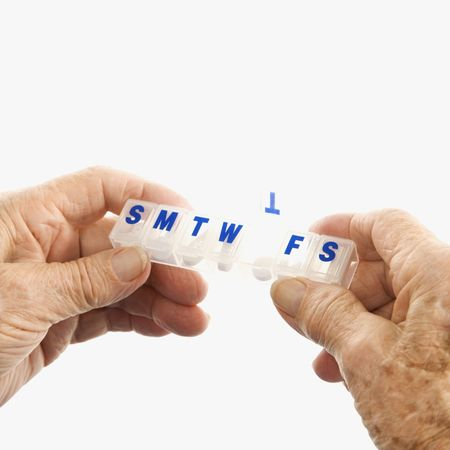 Caucasion elderly male hands holding seven-day pill box with Thursday open.  Stock Photo - 2246081
