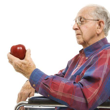 mela rossa: Profilo delluomo anziano di Caucasion che si siede in sedia a rotelle che guarda mela rossa in sua mano.