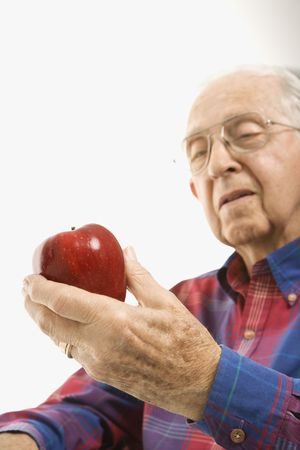 Caucasion elderly man looking at red apple in his hand. photo