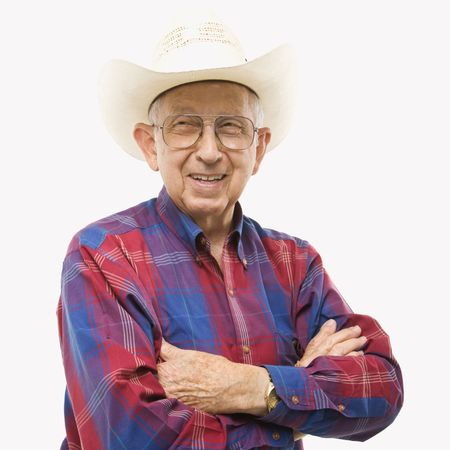 Portrait of smiling Caucasion elderly man wearing plaid shirt and cowboy hat with arms crossed. Stock Photo - 2389012