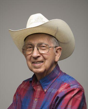 chemise carreaux: Portrait d'un homme �g� Caucasion souriant portait chemise � carreaux et chapeau de cow-boy. Banque d'images