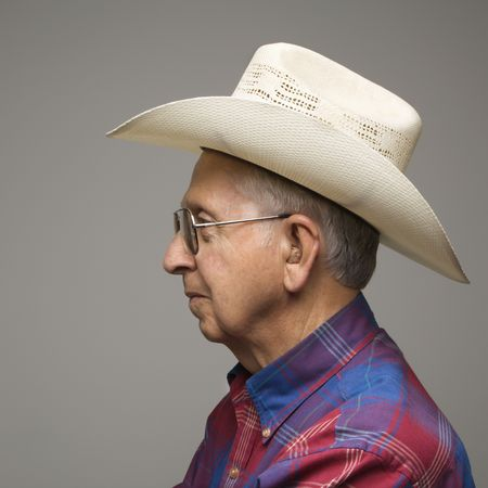 Profile portrait of elderly man wearing plaid shirt and cowboy hat. Stock Photo - 2388992