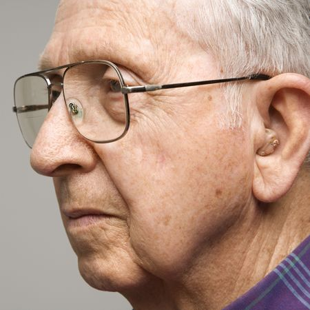 Close-up profile portrait of Caucasion elderly man with glasses and hearing aid. Stock Photo