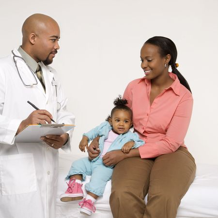 African-American mother and baby girl with male pediatrician.  photo