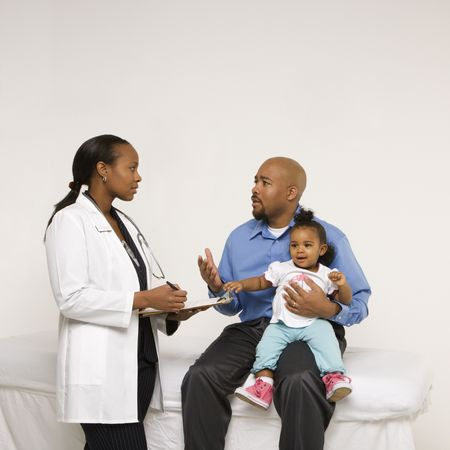 African-American father holding baby girl talking to female pediatrician. photo