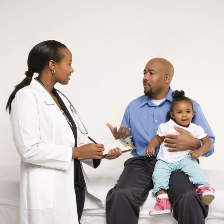 health concern: African-American father holding baby girl talking to female pediatrician.