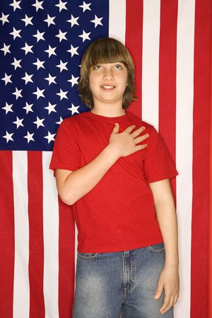 Portrait of Caucasian boy with hand over heart with american flag background. Stock Photo