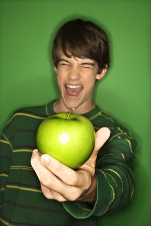 Portrait of Caucasian teen boy holding apple out in hand and making facial expression. photo