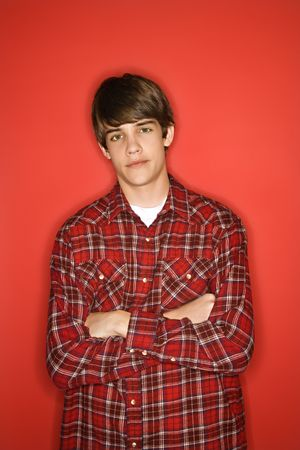 only one teenage boy: Portrait of Caucasian teen boy with arms crossed standing against red background wearing flannel shirt.