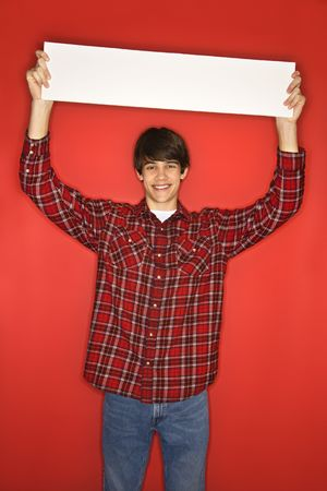 only one teenage boy: Caucasian teen boy holding blank sign above his head.