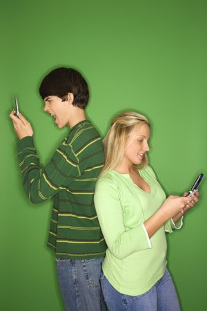 Portrait of Caucasian teen boy and girl on cellphones standing with backs to eachother against green background. Stock Photo - 2376374