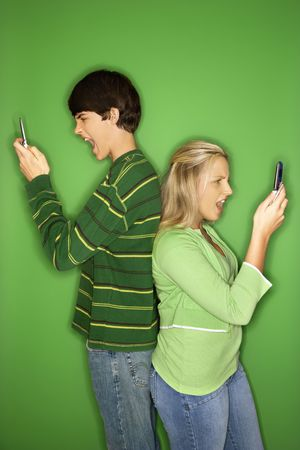 eachother: Portrait of Caucasian teen boy and girl on cellphones standing with backs to eachother against green background.