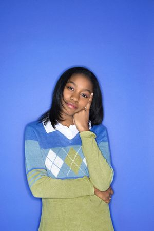 Portrait of African-American teen girl with head on hand standing against blue background. Stock Photo - 2376543